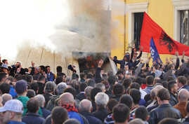 Albanian opposition supporters burn a bunker that would serve as the entrance of a former communist regime-used tunnel to be turned into a museum in Tirana, Dec. 8, 2015.