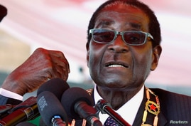 """Zimbabwe's President Robert Mugabe addresses the crowd gathered to commemorate Heroes Day in Harare August 12, 2013. Mugabe told critics of his disputed re-election to """"go hang"""" on Monday, dismissing his rivals as """"Western-sponsored stooges"""" at a lib"""