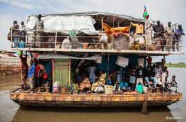 Southern Sudanese people arrive in a barge at the port in Juba, August 31, 2012.