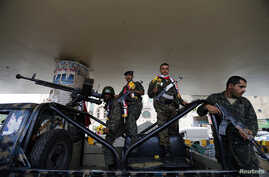 Police troopers stand on a police patrol vehicle stationed under a bridge in Sana'a, May 5, 2014, after they received flowers from activists showing their support for the military operation against al-Qaida militants in the south of the country.