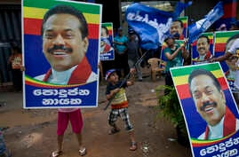 Supporters of Sri Lanka's former president and parliamentary candidate Mahinda Rajapaksa display his posters to mark conclusion of voting in Colombo, Sri Lanka, Monday, Aug. 17, 2015