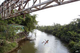 FILE - A youth jumps from an overpass into a river in Paragominas, northern state of Para, Brazil, Sept. 22, 2011. A Brazilian judge on Wednesday granted an injunction blocking a decree by President Michel Temer that opens up a vast Amazon area to mi