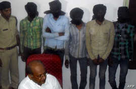 Indian Deputy Inspector General DK Arya (C) sits in front of five hooded suspects during a press meeting in Datia, about 75 kms from Gwalior in central Madhya Pradesh state, March 17, 2013.