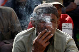 Hussain Jamal, a fisherman from India, smokes a cigarette as he sits with others, after their release from prison in Karachi, Pakistan, December 25, 2016.