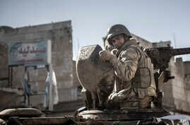 FILE - A soldier gives the thumbs up as Turkish army's armored vehicles and tanks roll into the Syrian town of Ayn al-Arab, Feb. 22, 2015.