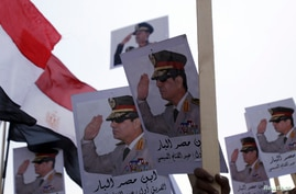 Posters of Army Chief General Abdel Fattah al-Sisi are seen as supporters of the army protest against ousted Islamist President Mohamed Mursi and members of the Muslim Brotherhood at the tomb of late Egyptian President Anwar Sadat, during the 40th an