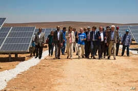 Officials from the IKEA Foundation, and the U.N. refugee agency tour a newly inaugurated solar energy plant, that will provide about 20,000 Syrian refugees with electricity, in the Azraq Refugee Camp, Jordan, Wednesday, April 17, 2017. The foundation