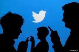 FILE - People holding mobile phones are silhouetted against a backdrop projected with the Twitter logo in this illustration.