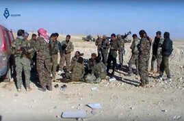 This frame grab from video provided by Qasioun a Syrian opposition media outlet, shows U.S.-backed fighters taking a rest during fighting with the Islamic State group near Ein Issa, north of Raqqa, Syria.