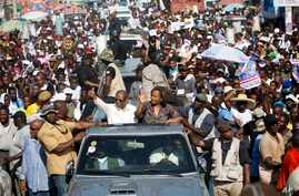 FILE -- Haiti's former President Jean-Bertrand Aristide, left, waves to supporters as he campaigns with presidential candidate Maryse Narcisse, of the Fanmi Lavalas political party, in Port-au-Prince, Haiti, in mid-September. Haiti will hold election