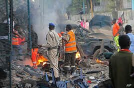 Somali soldier inspect wreckage of vehicles after a car bomb that was detonated in Mogadishu, Oct 28, 2017.