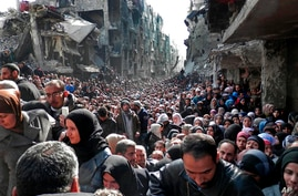 FOR USE AS DESIRED, YEAR END PHOTOS - FILE - This picture taken on Jan. 31, 2014, and released by the UNRWA, shows residents of the besieged Palestinian camp of Yarmouk, queuing to receive food supplies, in Damascus, Syria. A United Nations official