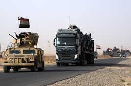 A convoy of Iraqi military vehicles heads toward Qayyarah base in northern Iraq, ahead of an expected offensive to retake Mosul from Islamic State militants, Oct. 15, 2016.