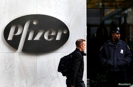 FILE - A man walks past the Pfizer logo next to a police officer standing outside Pfizer's world headquarters in New York.