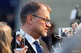 FILE - Finland's Prime Minister Juha Sipila talks to the media as he arrives for an informal meeting of European Union leaders, in Salzburg, Austria, Sept. 19, 2018.
