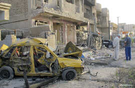 People inspect site of a car bomb attack in Baghdad, Iraq, Oct. 1, 2014.