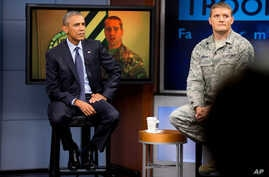 President Barack Obama, accompanied by Tech Sgt. Nathan Parry, takes a question from a service member in Afghanistan, on screen at center, during a town hall with service members at Fort Meade, Md., Sept. 11, 2015.