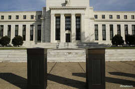 FILE - The U.S. Federal Reserve Board building is shown behind security barriers in Washington.