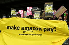 Demonstrators hold a banner and posters during a rally against the online retailer Amazon in Berlin, Germany, Nov. 24, 2017.