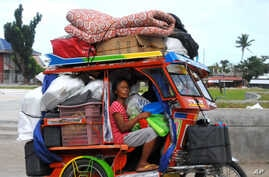 Typhoon survivors, some of whom are still living in tents, evacuate to safer grounds with their belongings at Tanauan township, Leyte province in central Philippines Thursday, Dec. 4, 2014, in anticipation of the incoming Typhoon Hagupit which is for