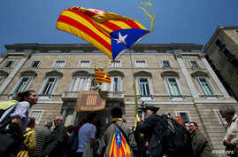 "FILE - A man waves an ""Estelada,"" Catalan separatist flag, outside the Generalitat Palace in Barcelona, Spain, May 17, 2018."