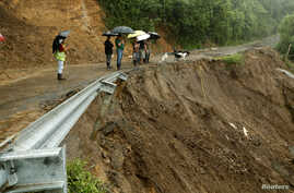 Residents look ta road partially collapsed by heavy rains of Tropical Storm Nate in El Llano de Alajuelita, Costa Rica, Oct. 5, 2017.