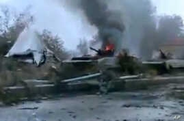 A Syrian military tank is shown as having caught fire outside Deir Ezzor in this January 29, 2013, file photo.