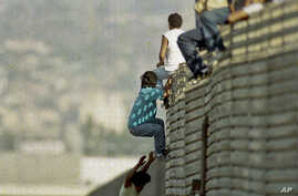 FILE - In this Oct. 14 1991 file photo, a group of illegal Mexican immigrants jump from a border fence to enter the United States, near Tijuana, Mexico.