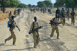 Sudan People's Liberation Army (SPLA) soldiers walk along a road in Mathiang near Bor, Jan. 31, 2014.