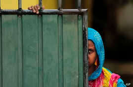 A Sri Lankan Muslim woman looks out on the street, in Aluthgama, town, 50 kilometers (31.25 miles) south of Colombo, Sri Lanka, June 16, 2014.