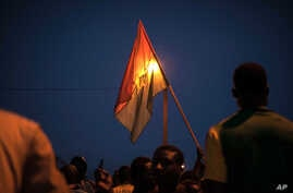 A protestor holds a Burkina Faso national flag during a protest against a recent coup in Ouagadougou, Burkina Faso, Sept. 21, 2015..