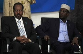 Somalia's newly elected President Hassan Sheikh Mohamud and his predecessor, Sharif Sheikh Ahmed (R), listen to proceedings after the election, in Mogadishu, Somalia, September 10, 2012.