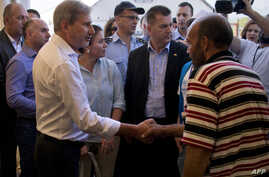 Commissioner for European Neighborhood Policy Johannes Hahn shakes hands with a migrant at a camp near Gevgelija on Sept. 19, 2015.