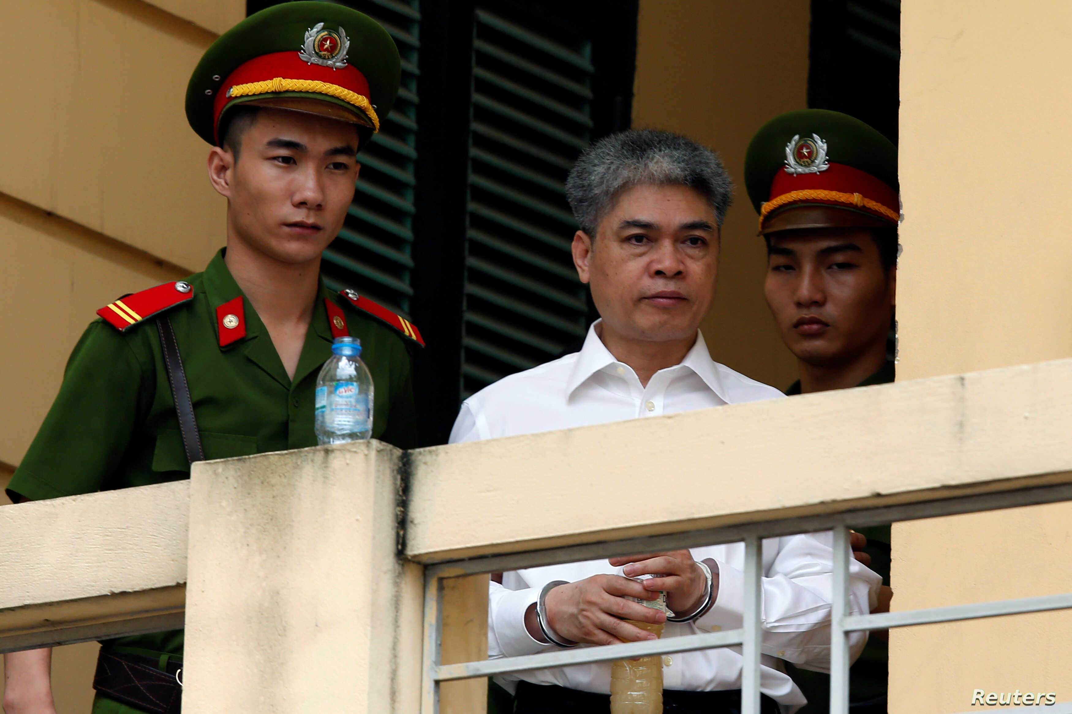 Former PetroVietnam chairman Nguyen Xuan Son is escorted by police as he leaves court after the verdict session in Hanoi, Vietnam, Sept. 29, 2017.