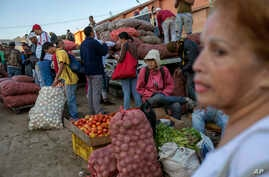 Vegetable vendors wait for customers at a wholesale food market in Caracas, Venezuela, Jan. 28, 2019.