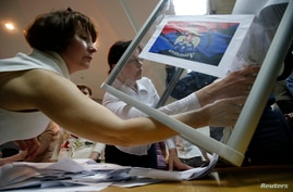 Members of a local election commission empty a ballot box as they start counting votes of the referendum on the status of Donetsk region in Donetsk, May 11, 2014.