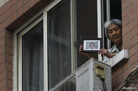 Zhang Xianling, whose son Wang Nan was killed by soldiers at the Tiananmen Square in 1989, holds his picture after journalists were turned away, at the window of her home in Beijing, April 24, 2014.