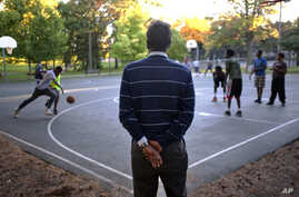 FILE - Abdirizak Bihi, right, executive director of the Somali Education and Social Advocacy Center, watches kids play basketball at Currie Park in Minneapolis, near a large Somali community in the Cedar Riverside neighborhood, Sept. 22, 2014.
