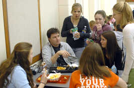 Scott Greene, sitting at left, facing camera, a youth minister with the Warsaw Community Church is surrounded by students at lunch at Warsaw High School, March 9, 2006, in Warsaw, Ind.