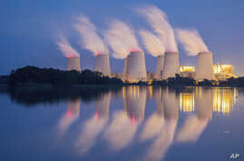 FILE - In this Sept. 19, 2018 photo steam and cooling towers of a lignite power plant are reflected in a pond in Peitz, eastern Germany.