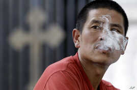 A man blows out cigarette smoke outside a church in Beijing, (File 2010)