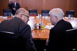 German Interior Minister Horst Seehofer, right, talks with Economy Minister, Peter Altmaier, left, prior to the last cabinet meeting of the German government for this year, at the chancellery in Berlin, Wednesday, Dec. 19, 2018.