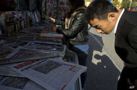 "A man looks over near the front page of a Chinese newspaper showing a photo of the typhoon damage in the Philippines and the white characters on blue which reads ""U.S. and Europe hype up Chinese aid to Philippines as 'Not Generous'"", at a newsstand i"