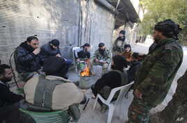 Rebel fighters of al-Jabha al-Shamiya (Levant Front) warm themselves around a fire near the justice palace in the old city of Aleppo, Syria, Jan. 28, 2016.
