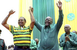 Tanzania's public works minister John Pombe Magufuli, right, celebrates with President Jakaya Kikwete, left, after the ruling party announced its presidential candidate, in Dodoma, Tanzania, July 12, 2015.