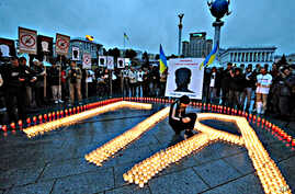 A person lights a candle to help form the name Giya, nickname of Georgy Gongadze, during a memorial rally on Independence square in Kiev (file photo - 16 Sep 2008)