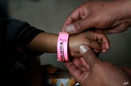 A child wears a bracelet marked with a number that indicates his place in line to submit his request for U.S. asylum, inside a shelter at Bachilleres gymnasium in Ciudad Juarez, Mexico, Feb. 19, 2019.