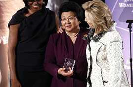 U.S. first lady Michelle Obama (L) and Secretary of State Hillary Clinton (R) honor Kyrgyzstan President Roza Otunbayeva during the International Women of Courage Awards Ceremony at the State Department, March 8, 2011