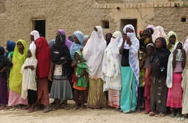 FILE - In this Aug. 31, 2012, photo, women and girls, wearing veils to comply with the dictates of Islamist group Ansar Dine, are forced to attend a public lashing in Timbuktu, Mali.