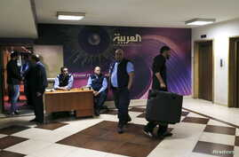 Watched by security personnel, a man carrying a suitcase leaves the shuttered offices of Saudi-owned TV news channel Al Arabiya in Beirut, Lebanaon, April 1, 2016.
